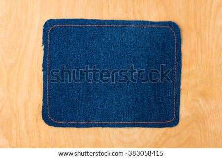 Dark frame made of denim is lying on a light wood surface