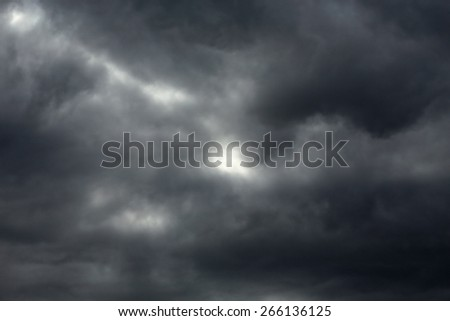 Dark gray and black clouds with some light  - stock photo
