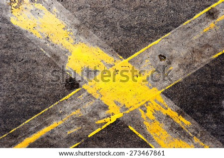 Dark grey asphalt background with yellow paint  - stock photo