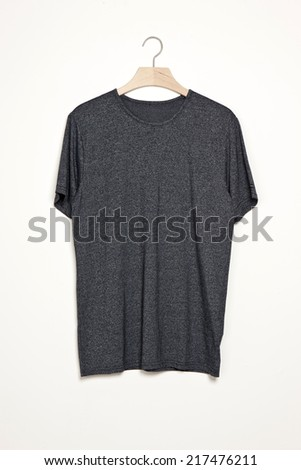 Dark grey t-shirts with wood hanger isolated white. - stock photo