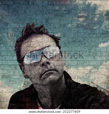 Dark Grunge image of a Man with Blue Sky and Clouds painted on a Brick wall - stock photo