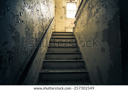 Dark grungy staircase with bright window in abandoned home - stock photo