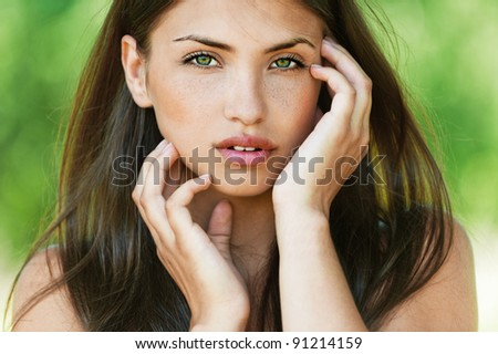 dark hair and beautiful sexy girl with bare shoulders seductively posing with his hands touching face - stock photo