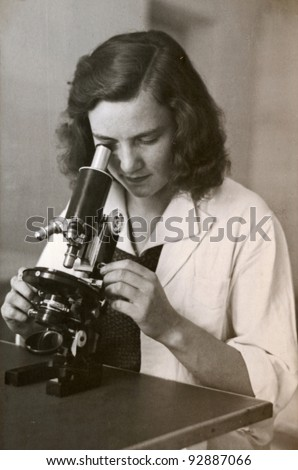 dark hair girl with the microscope - photo scan - about 1955 - stock photo