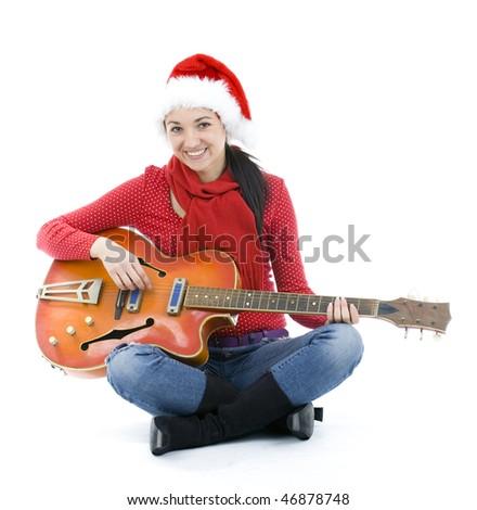 dark hair young woman in Santa cap playing electric guitar - stock photo