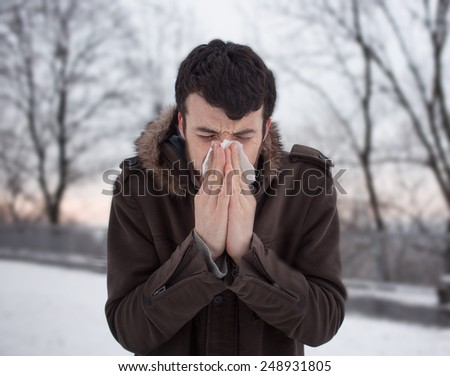 dark-haired bearded man Blowing His Nose  in winter park  - stock photo
