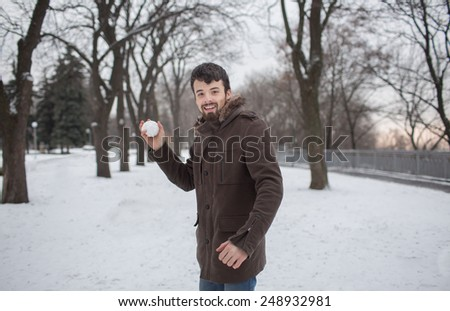dark-haired bearded man in a gray coat throwing snowballs  in snow park  - stock photo