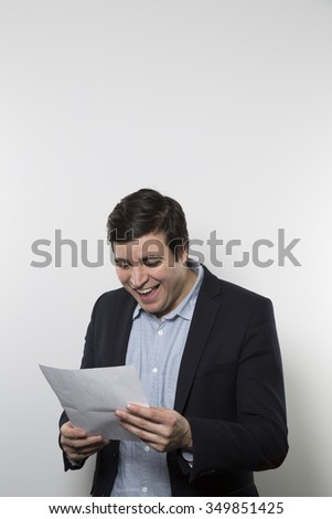 Dark-haired european businessman with a happy look and a good laugh stares at a piece of paper while in front of a gradient background