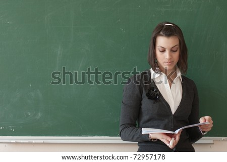 Dark-haired female student reads a notes of the board. - stock photo