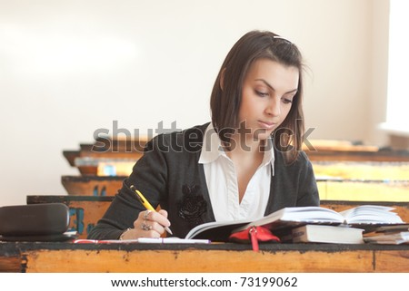 Dark-haired female student sitting at a desk and biting pen. - stock photo