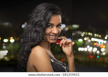 dark-haired girl at city background with casino chips - stock photo