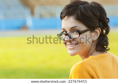 Dark-haired girl in glasses against autumn. - stock photo