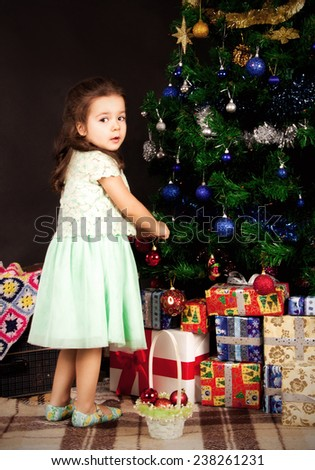 dark-haired girl standing near the Christmas tree and hang toys looking away - stock photo