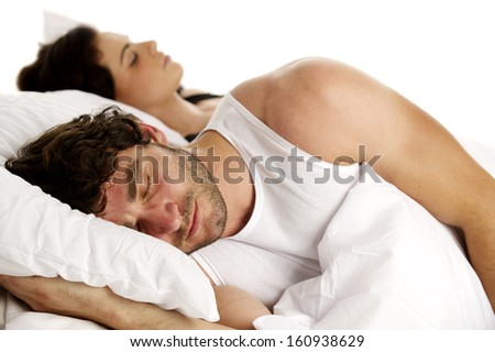 Dark haired male laid in a white bed sleeping next to his girlfriend isolated on a white background