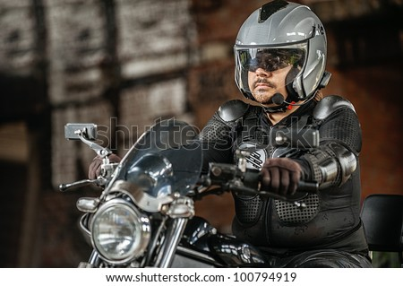 Dark-haired man sitting sitting on his motorcycle.