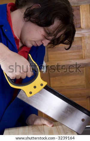 Dark haired man with blue overall holding saw with wooden board - stock photo