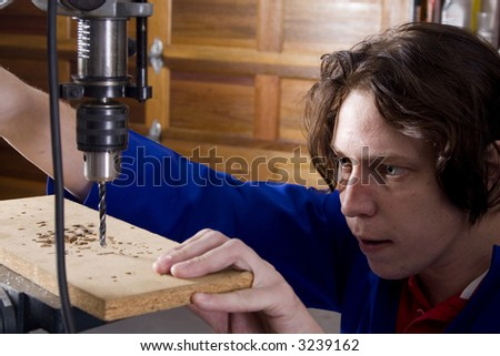 Dark haired man with blue overall using drill machine - stock photo
