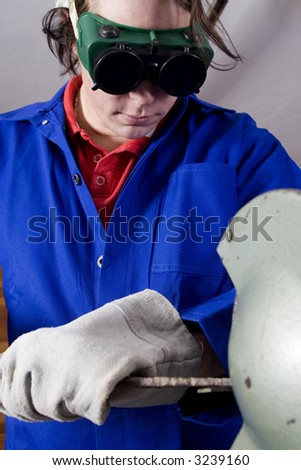 Dark haired man with blue overall using grinder with focus on handyman - stock photo