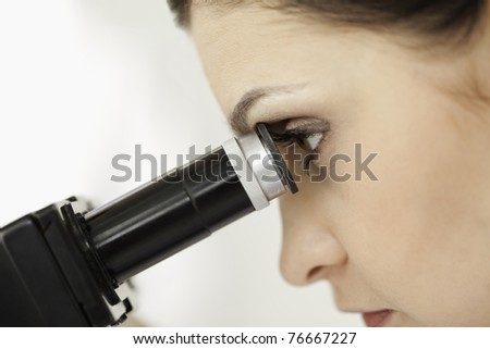 Dark-haired scientist looking through a microscope in a lab