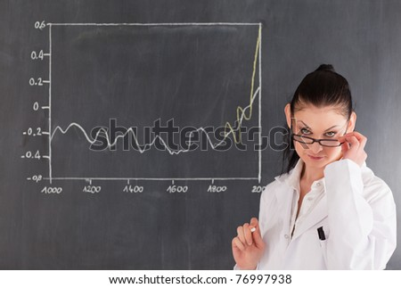 Dark-haired scientist standing near the blackboard and looking at the camera