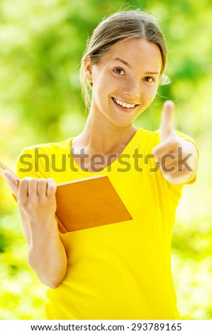Dark-haired smiling beautiful young woman in yellow blouse and with books lifts thumb upwards, against green of summer park. - stock photo