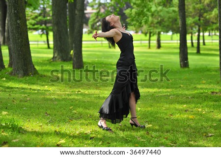 dark haired woman in wooded area - stock photo