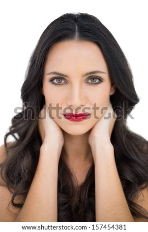 Dark haired woman with red lips touching her neck on white background - stock photo
