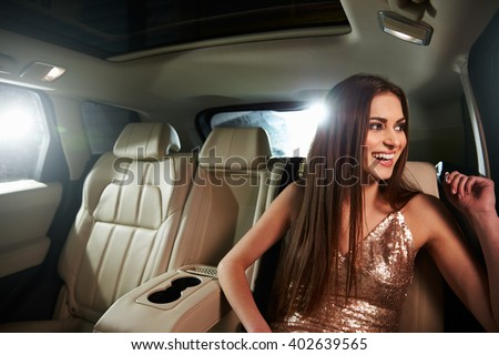 Dark haired young woman sitting in limo looks out of window - stock photo