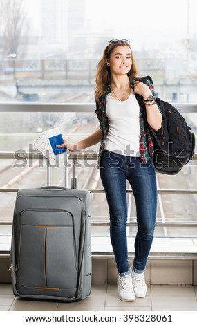 dark-haired young woman standing with a suitcase and a backpack and holding a passport with a ticket. Full length. tourism concept - stock photo