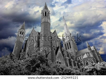 Dark haunted church converted to black and white with dark moody coloured storm clouds - stock photo