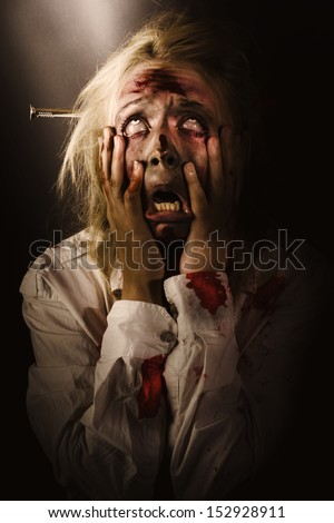 Dark horror portrait of a dying bloody zombie griping face with hands in fear and terror while looking up to the light. A passing scream between heaven and hell - stock photo