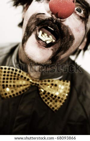 Dark Image Of A Clown Laughing With A Mouthful Of Capsules In A Dose Of Laughter - stock photo