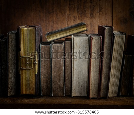 dark image of antique books on wooden shelf. - stock photo