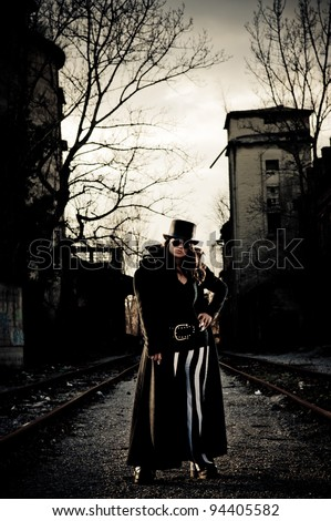 Dark image of scary woman standing between railroad tracks - stock photo