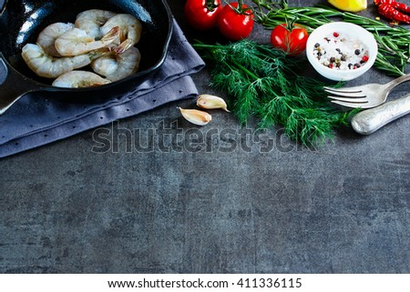 Dark kitchen table with raw ingredients for preparing fresh seafood (shrimp, tomatoes, fresh herbs and spices) on vintage background, selective focus, space for text. - stock photo
