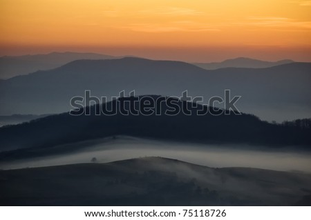 dark landscape with fog between hills and orange sky before sunrise - stock photo