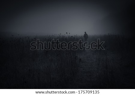 dark landscape with man walking at night - stock photo