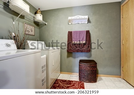 Dark laundry room interior with white appliances and wicker basket - stock photo
