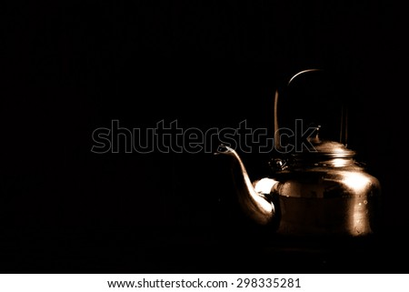 Dark light still life of old aluminium kettle - stock photo