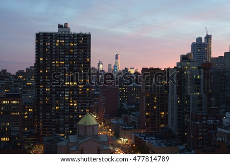 Dark Manhattan New York cityscape, colorful sunset. Colorful sky. Long exposure light streaks from cars on streets.