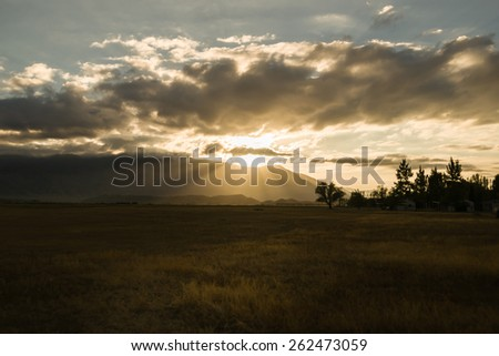 Dark moody landscape with Benmore Range catches rising sun Omarama, Central Otago  The dry golden field catches sunlight in foreground. - stock photo