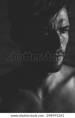 Dark moody portrait of an intense young man with a goatee frowning as he looks to the side, close up of his face and wet bare shoulders - stock photo