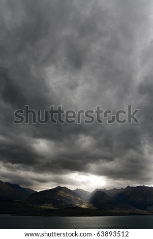 Dark moody sky over mountain range, new zealand - stock photo