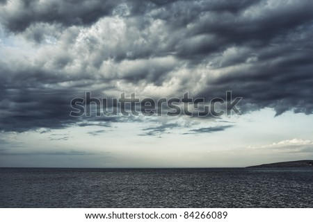 Dark moody sky over the gray sea. - stock photo