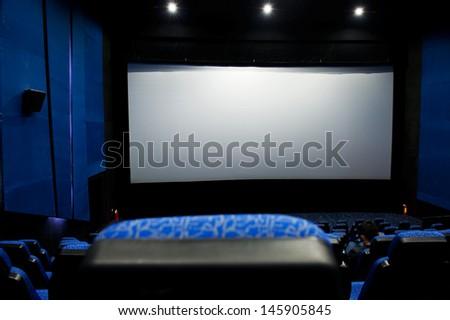 Dark movie theatre interior. screen and chairs. - stock photo