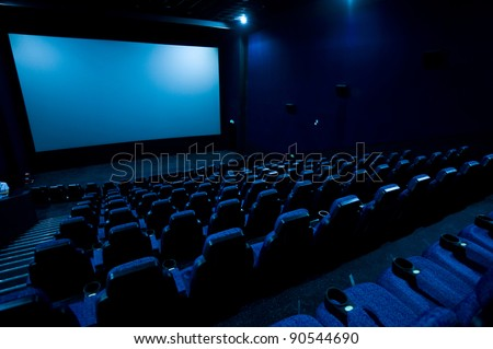 Dark movie theatre interior. screen, chairs - stock photo