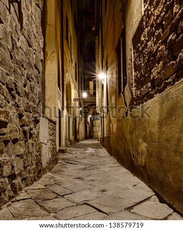 dark narrow alley at night lit by old street lamps in Florence, Tuscany, Italy - stock photo