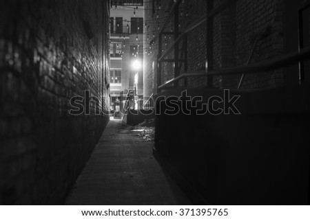 dark narrow alleyway at night, with street light illuminating the scene - stock photo