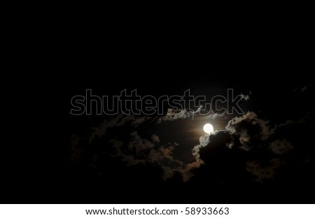 Dark night sky with the moon surrounded by highlighted clouds. - stock photo