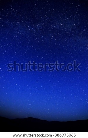 Dark nights sky with galaxies and mountains